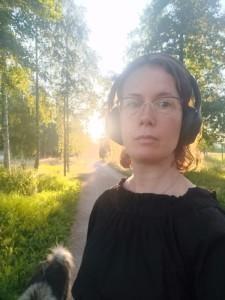Elina Hellqvist kävelee ilta-auringossa kuulokkeet korvillaan koiran kanssa pitkin kävelytietä.